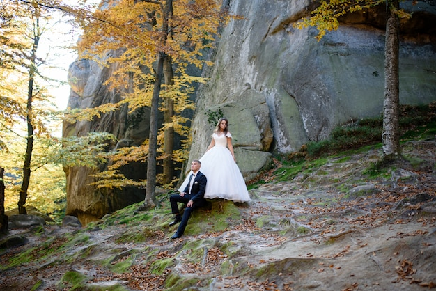 Newlyweds are sitting on the background of the cliff.