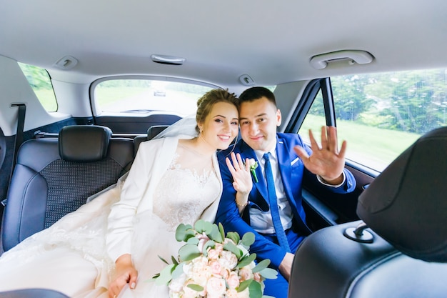 Newlyweds are sitting in the car looking at the camera