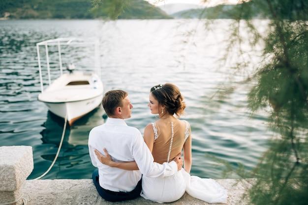白いモーターボートが背景に結ばれている桟橋に新婚夫婦が抱きしめて座っている