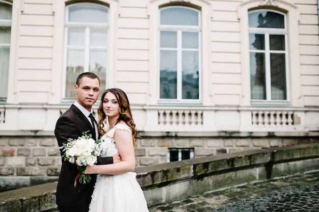 Newlyweds are stand near ancient architecture, building, old house outside, vintage palace outdoor. romantic love in vintage atmosphere street.
