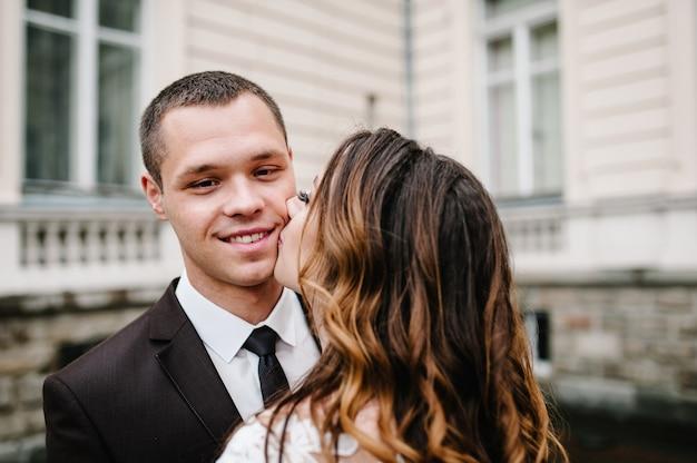 Молодожены стоят и целуются возле старого дома на улице. свадебная церемония.