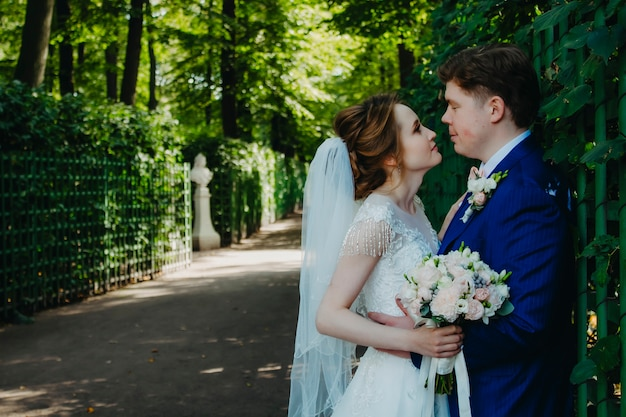 Newlyweds are walking in the park on their wedding day.