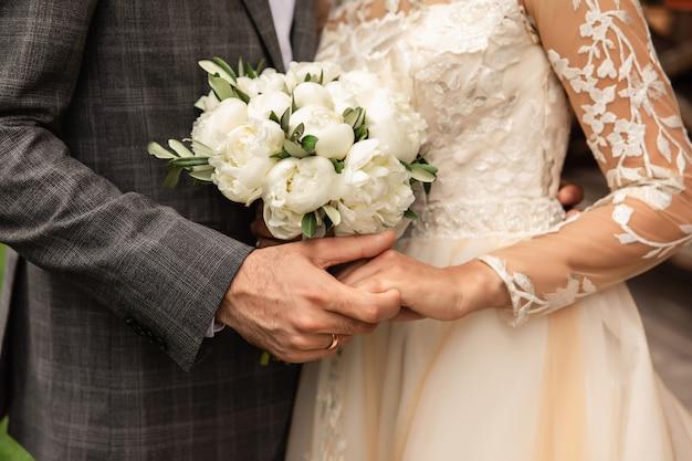 結婚式の日に新婚夫婦、結婚式の花束を持つ結婚式のカップル