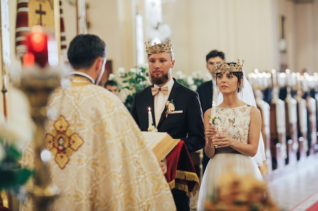 Newlyweds in the church. priest celebrate wedding mass at the church
