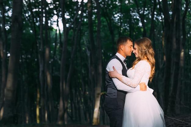 新婚夫婦は目を閉じ、お互いの腕の中で