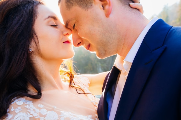 Newlyweds closed their eyes and lean their heads.