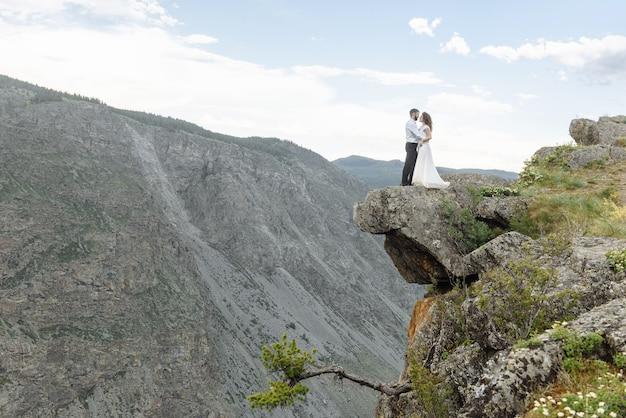 山のウェディングドレスを着た新婚夫婦のカップルの男性新郎と女性の花嫁は、石の峡谷の上に一緒に立っています