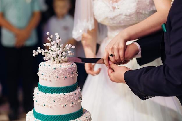 新婚夫婦がウエディングケーキを切るナイフを一緒に持って、ケーキを一緒に切るクローズアップ