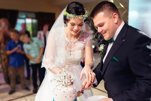 新婚夫婦がバックグラウンドでレストランホールのゲストでウエディングケーキをカット