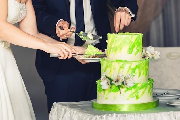 신혼 부부는 녹색의 결혼식 3 단 케이크를 자릅니다.