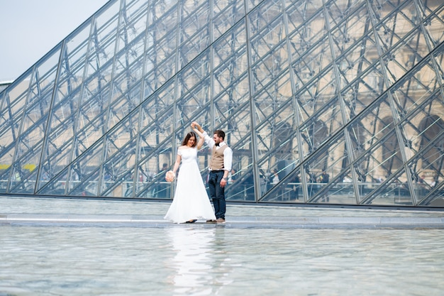 Newlyweds dancing in front of louvre museum
