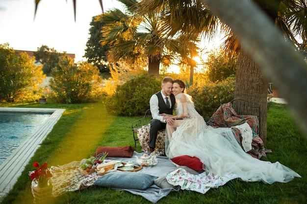 신혼부부는 해질녘 잔디밭에서 저녁식사를 한다. 프랑스에서 해질녘에 한 커플이 앉아서 차를 마신다