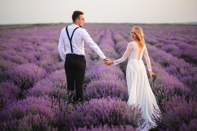 Newlyweds dressed in country style walk holding hands along a flowering field of lavender