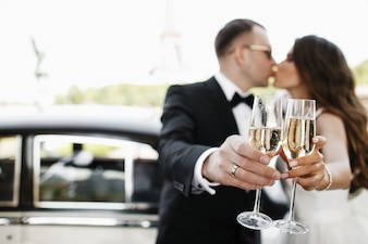 Newlyweds drink champagne standing before a retro car