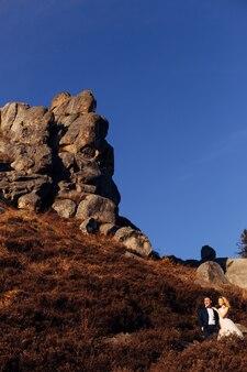 新婚夫婦は山の頂上にある石の崖の背景の景色を受け入れ、賞賛します