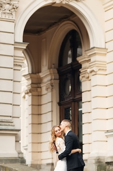 Молодожены обнимаются и закрывают глаза, красивое здание. жених целует невесту.