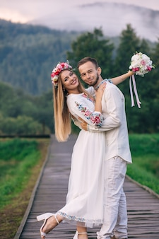 Newlyweds in embroidered clothes hugging and looking at the camera on the background of mountains and fog.