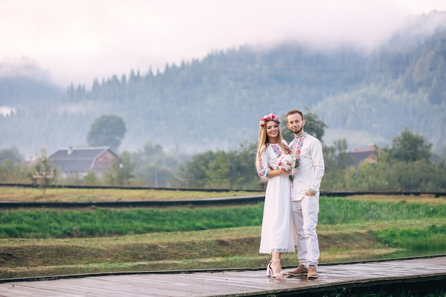 Newlyweds in embroidered clothes look at camera on he background of mountains and fog. bride holding wedding bouquet.