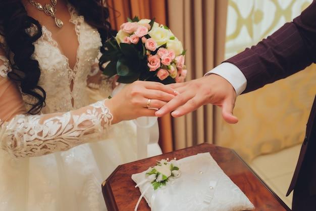新婚夫婦は指輪を交換し、新郎は結婚登録事務所で花嫁の手に指輪を置きます。