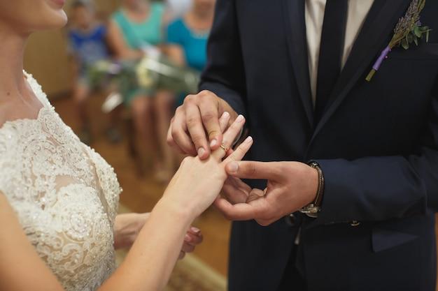 Молодожены обмениваются кольцами, жених надевает кольцо на руку невесты в загс