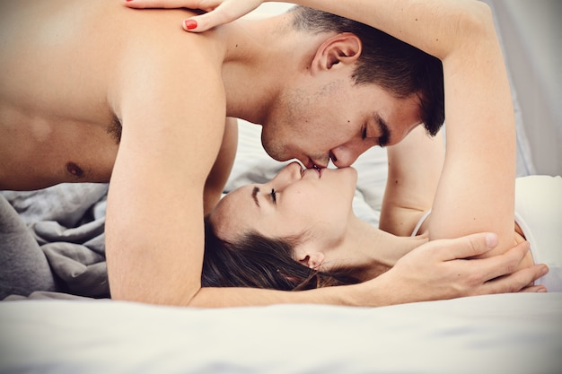 Newlyweds gently kissing in bed in the early morning