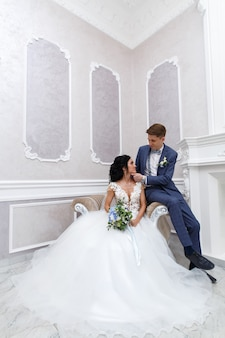 Newlyweds gently look at each other . portrait  bride anf groom hugging in a wedding ceremony in a stylish interior. happy weeding day