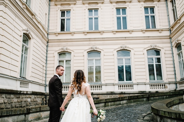 Newlyweds go back to the ancient restored architecture, vintage palace outdoor.