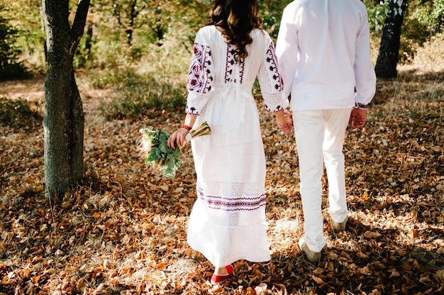 Молодожены возвращаются в осенний парк. украинский стиль: женщина, мужчина в вышитой одежде с букетом цветов гуляют по природе. этническая свадьба в национальных костюмах.