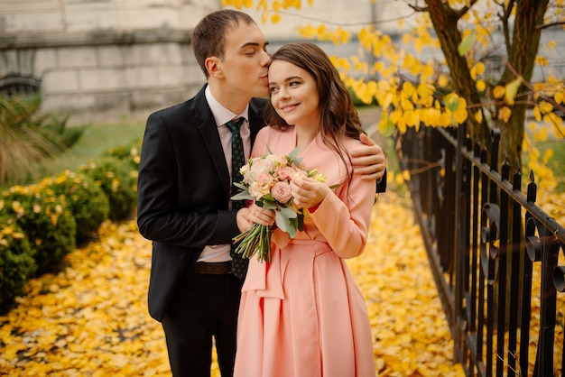 Newlyweds groom and bride walking in autumn park near vintage atmosphere gothic cathedral. wedding, love concept.