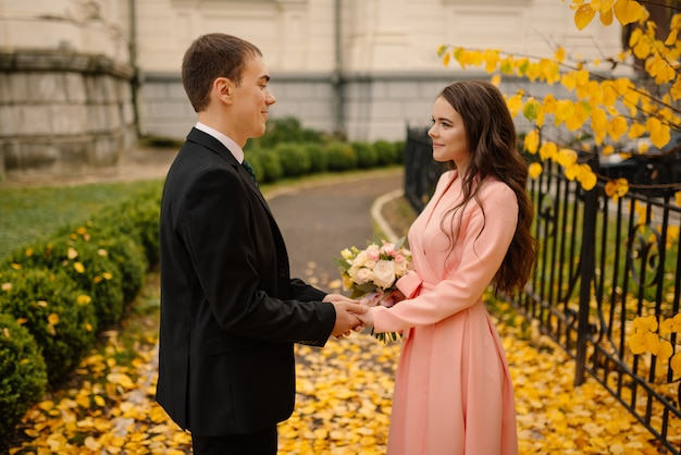 Newlyweds groom and bride walking in autumn park near vintage atmosphere gothic cathedral.