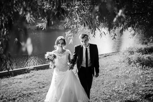 新婚夫婦。幸せな結婚式のカップル。池の近くの公園を歩いている新郎新婦。白黒画像