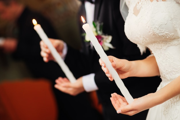 The newlyweds hold candles on their hands in the church
