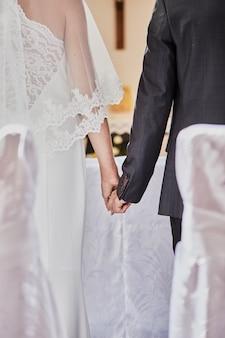 신혼 부부는 가톨릭 교회에서 결혼식 중에 손을 잡습니다.