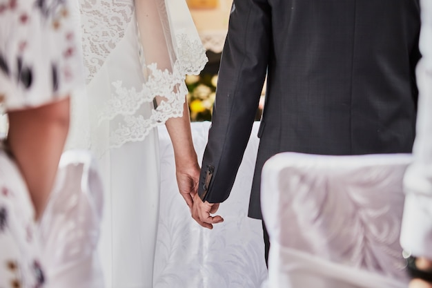 Newlyweds hold hands during a wedding in a catholic church