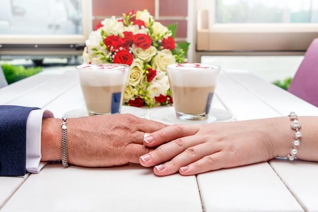 新婚夫婦は手をつないでいます。新婚夫婦、コーヒー、白いテーブルの上のウェディングブーケを手します。カフェの新婚夫婦が結婚式を祝う