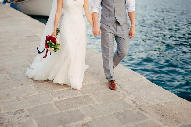 Молодожены держатся за руки на море пара, взявшись за руки свадьба