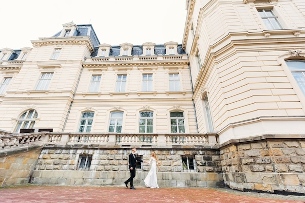 The newlyweds hold hands and walk near the beautiful palace. ancient palace with beautiful architecture and many windows.