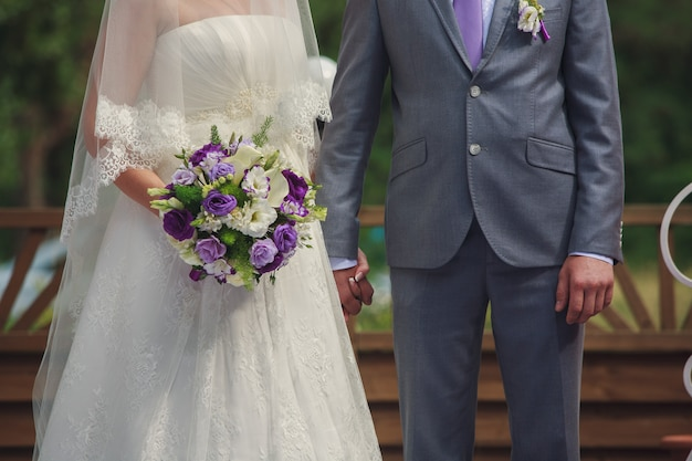Newlyweds holding hands at sunny wedding day.