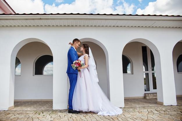 Newlyweds hug and kiss near lighthouse at wedding