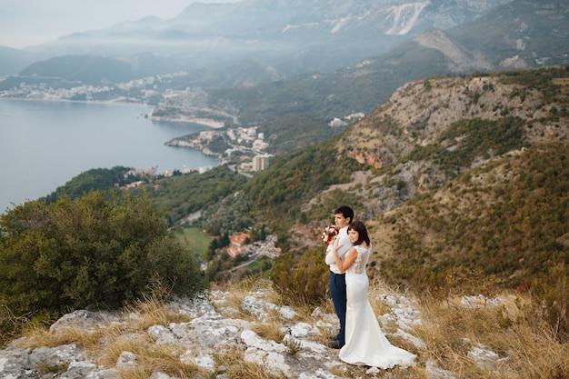 Молодожены обнимаются на панораме города будвы горы и море