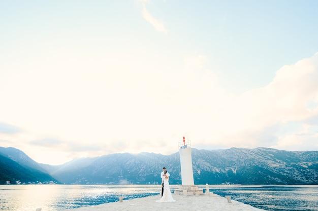 Молодожены обнимаются на острове госпа од скрпела на фоне маяка