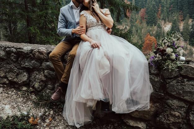 岩、石、木々を背景に抱き締める新婚夫婦。
