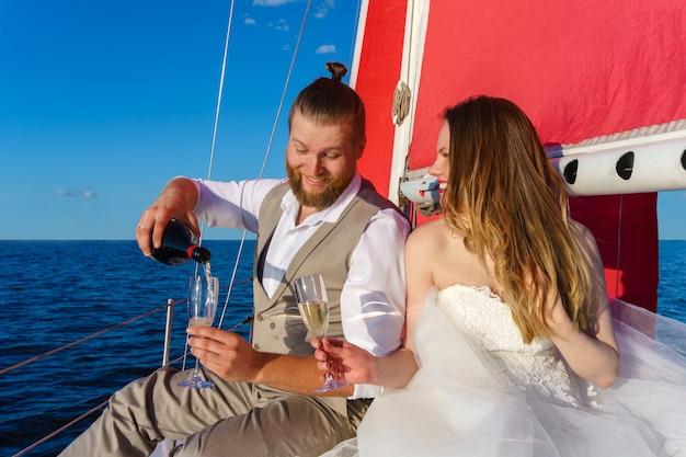 Молодожены в свадебном путешествии к морю на парусной яхте, разливая игристое вино.