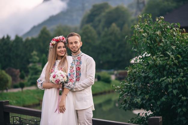 Молодожены в вышитых одеждах улыбаются и смотрят в камеру на фоне гор и озер.