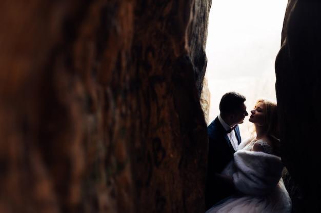 Молодожены в праздничных нарядах закрыли глаза и хотят поцеловаться в каменном туннеле.