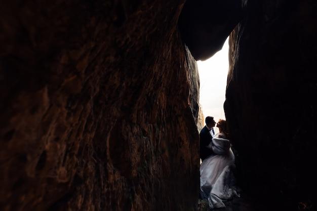 Молодожены в праздничных нарядах хотят поцеловаться на свадьбе в каменном тоннеле