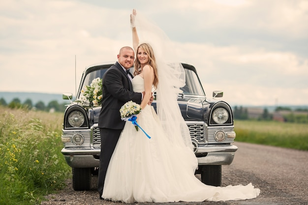 車の前で新婚夫婦
