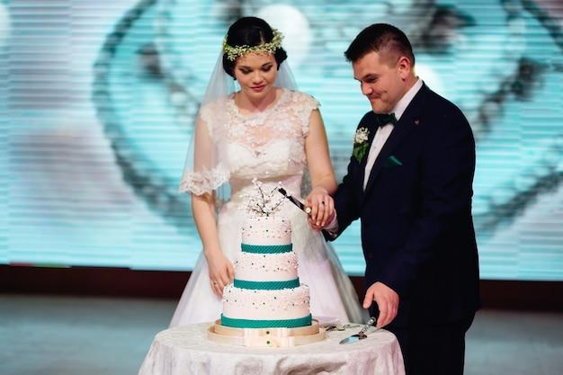 レストランのホールにいる新婚夫婦がウエディングケーキを持ってテーブルに立ってウエディングケーキを切った
