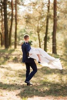 공원에있는 신혼 부부. 신랑은 신부를 팔과 원에 안고 있습니다.