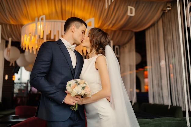 Молодожены целуются, держа в руках букет. свадьба, любовь, концепция отношений.